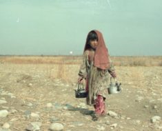A young girl carrying clean drinking water, 1989